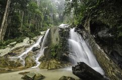 Amazing scenery of tropical waterfall flowing through the beautiful green forest. Selective focus shot royalty free stock image
