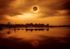 Amazing scientific natural phenomenon. The Moon covering the Sun. Total solar eclipse with diamond ring effect glowing on sky. Above silhouettes of trees, river royalty free stock image