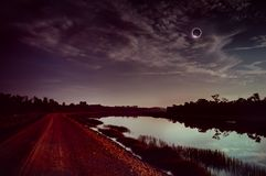 Amazing scientific natural phenomenon. The Moon covering the Sun. Total solar eclipse with diamond ring effect glowing on sky royalty free stock images