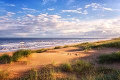 Free Amazing Seascape In Soft Sunset Light With Sand Dunes, Green Grass, Waves Of The Sea And Blue Sky With Clouds, Travel Background Royalty Free Stock Photo - 167040895