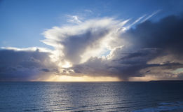 Amazing seascape with sunset rays behind clouds over ocean Stock Photo