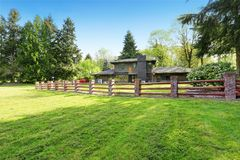 Amazing secluded home with large fenced backyard area,. Amazing secluded home with large fenced backyard area featuring a lush green lawn and surrounded by trees Stock Photo