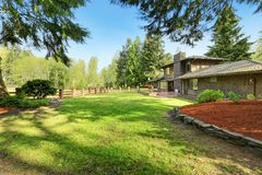 Amazing secluded home with large fenced backyard area,. Amazing secluded home with large fenced backyard area featuring a lush green lawn and surrounded by trees Stock Images