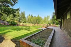 Amazing secluded home with large fenced frontyard area,. Amazing secluded home with large fenced frontyard area featuring a lush green lawn and surrounded by Royalty Free Stock Photography