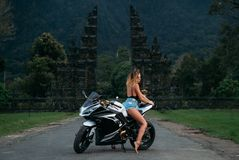 Amazing sexy girl sits on a motorcycle in black and white. A model dressed in a black jersey and denim shorts posing on. A bike. woman Motobike drivers Stock Photography