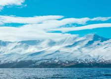 Amazing shot of snowy mountains and the sea stock photos