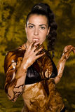 Amazing shot of a young beautiful brunette with her naked body covered of sweet cream chocolate Royalty Free Stock Image