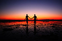 Amazing silhouette of couple walking hand in hand on sunset background. Two people in love walking on the beach Royalty Free Stock Photos