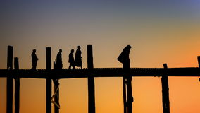 Amazing silhouettes of monks on the ancient wooden bridge at sunset sky background. Burma, Mandalay stock footage