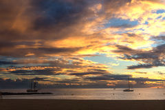 Amazing sky at sunset on the beach. Boats in the sea at sunset. Royalty Free Stock Photography