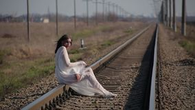 Amazing girl in white translucent dress blown by wind and with wax makeup on face in form of bloody wound sits on railroad tracks. Amazing slim unusual beautiful stock video footage