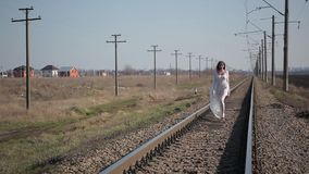 Girl in white translucent dress blown by wind and with wax makeup on face in form of bloody wound goes at camera on railroad. Amazing slim unusual beautiful girl stock video footage