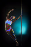 Amazing slim woman with UV makeup dancing on pole Royalty Free Stock Images