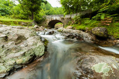 Amazing small waterfall on a stone bridge background Stock Photography