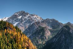 Amazing snow-capped mountains on blue sky background. Amazing snowy peaks and wooded mountains in autumn. Scenic fall landscape in Jiuzhaigou nature reserve stock images