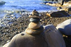 Amazing stack of stones on green moss at seaside beach group of pebble balance on large rock. As meditation concept for Zen or strong mind or teamwork spirit Stock Photos
