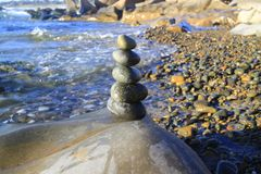 Amazing stack of stones on green moss at seaside beach group of pebble balance on large rock. As meditation concept for Zen or strong mind or teamwork spirit Royalty Free Stock Image