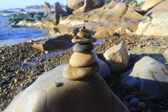 Amazing stack of stones on green moss at seaside beach group of pebble balance on large rock Stock Images