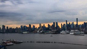 Amazing steady time lapse panorama of gray rain clouds moving in evening orange sunset sky over New York ocean cityscape. Amazing steady time lapse panorama of stock footage