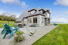 Amazing stone house with a patio area view. VIew of the big stone house with concrete floor patio area royalty free stock images