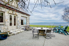Amazing stone house with a patio area view. VIew of the big stone house with concrete floor patio area. Patio table set and deck chairs royalty free stock image