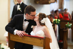 Amazing stylish cute groom and bride is kissing on the backgrou. Nd old gothic church royalty free stock images