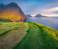 Amazing summer scene from Sunset Viewpoint in Gasadalur village. Fantastic evening landscape of Vagar island with Tindholmur cliff