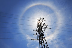 Amazing sun halo above power supply network. Amazing sun halo above high-voltage power supply network Royalty Free Stock Images