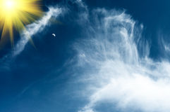 Amazing sun and moon high in  the blue sky. Stock Photo