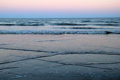 Amazing sunrise with gentle waves lapping the shore, pinks and purples greeting the morning. Pinks and purples of an early morning sunrise at the beach, with royalty free stock photography