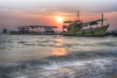 Amazing sunrise over the beach with boat stock image