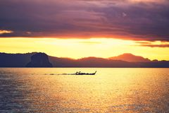 Amazing sunrise on the sea. Silhouette of a small fishing boat against tropical islands between Phuket and Krabi in Thailand Royalty Free Stock Photos