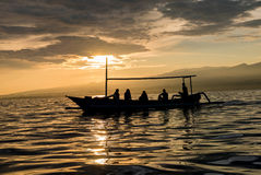Amazing sunrise with silhouette of people in small boat in Lovin Royalty Free Stock Photography