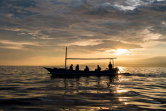 Amazing sunrise with silhouette of people in small boat in Lovin Stock Photography
