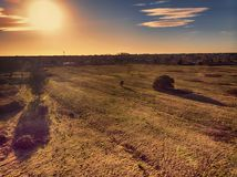 Amazing sunset aerial view up countryside above meadow and trees with relaxing atmosphere stock photos
