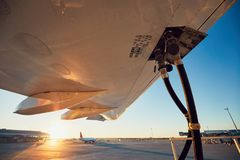 Refueling of the airplane. Amazing sunset at the airport. Refueling of the airplane before flight royalty free stock images