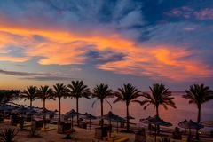 Amazing Sunset on the Beach with Parasols and Palm Trees at Calimera Habiba Beach Resort stock images