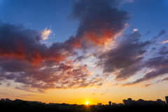 Amazing sunset at city. Dramatic sky with clouds. Royalty Free Stock Image
