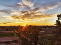 Amazing sunset in the countryside above the cultivated fields and the sun between trees spreads its rays. In a wonderful cloudy day royalty free stock photography