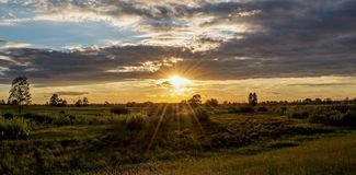 Amazing sunset with dark blue clouds in the field at the village. In Ukraine Royalty Free Stock Images