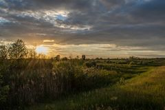 Amazing sunset with dark blue clouds at the meadow at the village. In Ukraine Royalty Free Stock Photo