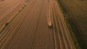 Amazing sunset footage of Combine Harvester harvesting wheat fields in UK. Aerial 4K footage shot in August. Farmers work the field in Yorkshire, UK at the end stock video