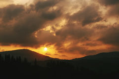 Amazing sunset in mountains landscape, sun and clouds and woods Stock Photography