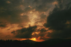Amazing sunset in mountains landscape, sun and clouds and woods Stock Photos