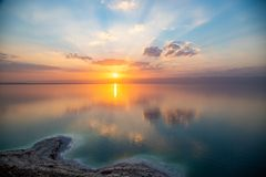 Sunset over Dead sea, view from Jordan to Israel and Mountains of Judea. Reflection of sun, skies and clouds. Salty beach, salt. royalty free stock images