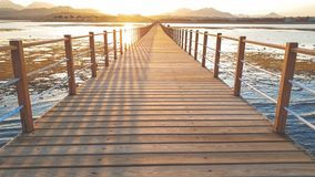 Amazing sunset over the long wooden pier in calm ocean. Sea waves rolling on breaking on the wooden bridge royalty free stock photos