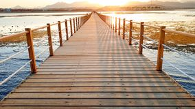 Amazing sunset over the long wooden pier in calm ocean. Sea waves rolling on breaking on the wooden bridge royalty free stock images