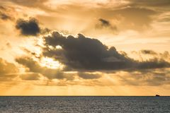 Amazing sunset over the ocean, sun hidden by the thick clouds, f Royalty Free Stock Images