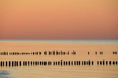 Amazing sunset over the sea. Baltic. Red, pink, violet, orange and dark blue light. The sky is reflected in the calm sea. Old wooden breakwaters are Royalty Free Stock Photos