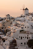 Amazing Sunset over white windmills in  town of Oia and panorama to Santorini island, Thira, Greece Stock Photos